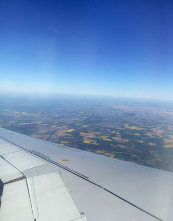 viewport: Airplane wing and land far under the plane. Flight in the deep blue sky