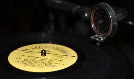 phono: Black vinyl disc rotating on a gramophone, retro background
