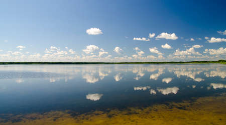 Clouds reflecting in pure lake water, gorgeous sky and clouds over mirror of lake water panorama