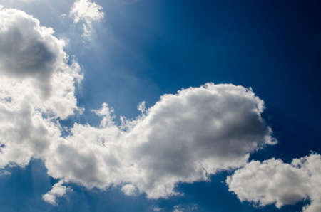 Blue sky with white clouds in sun rays, pure sky background