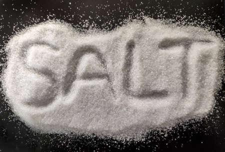 Foto conceptual de sal, sal blanca aislada sobre fondo negro. Sal natural para cocinar y spa con letras. Vista de cerca aislada