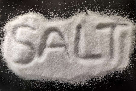 Photo conceptuelle de sel, sel blanc isolé sur fond noir. Sel naturel pour la cuisine et le SPA avec des lettres dessus. Vue rapprochée isolée