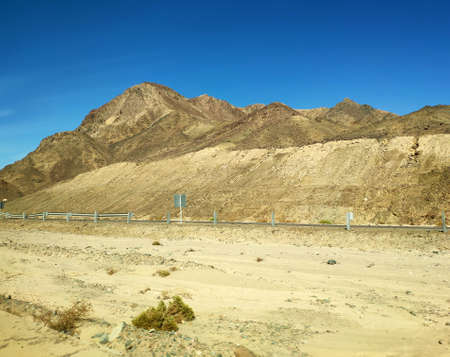 Road going through Sinai desert, picturesque backgound with mountains and hills, desert landscape wallpaper Фото со стока