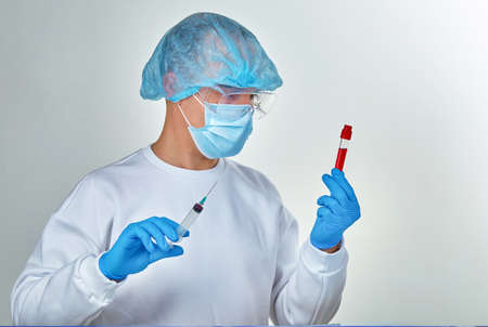 Doctor in mask holding the blood test tubes, coronavirus COVID19, HIV, ebola or other dangerous infection. Medical background, instruments, template, wallpaper. Coronavirus disease concept. Doctor portrait