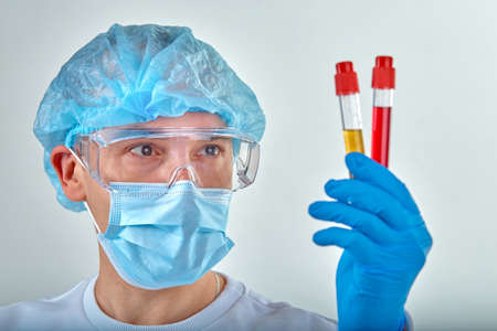 Doctor in mask performing blood test for coronavirus COVID19, HIV, ebola or other dangerous infection. Medical background, instruments, template, wallpaper. Coronavirus disease concept