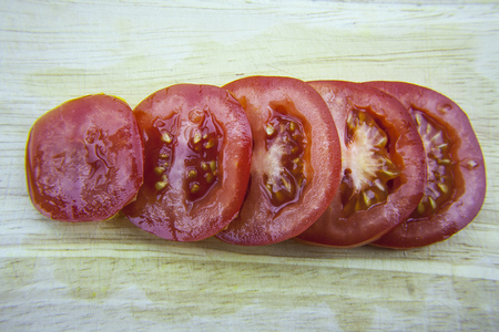 Sliced tomatoes laying on wooden desk. Delitious red tomates. Banco de Imagens
