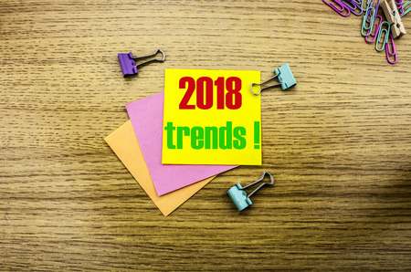 Trends 2018 text on yellow sticky note on wooden background. Minimal concept. 2018 trends.