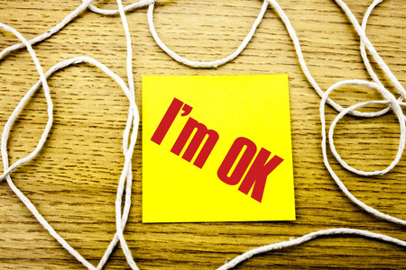I am OK word on yellow sticky note in wooden background. Bussines concept. Motivational. Stock Photo