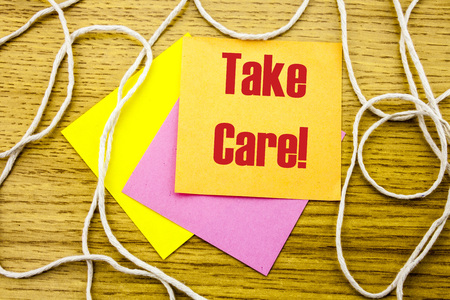 Take care- word on yellow sticky note in wooden background. Bussines concept. Motivational.