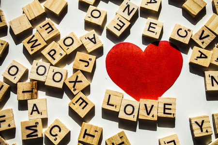WORD LOVE. Wooden letters spelling the word LOVEon white background with red heart.