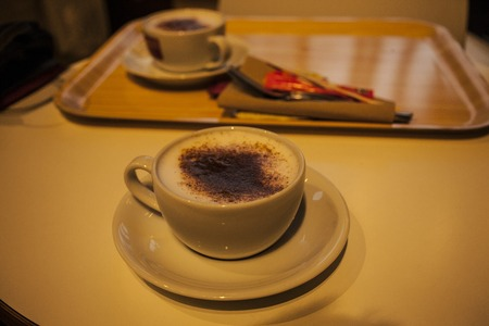 Cup of cappuccino with newspaper on the table, coffee shop background, warm tone