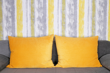 couch: Couch with yellow pillows and wallpaper