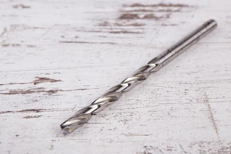 hard alloy: Drill bit on wooden grunge background Stock Photo
