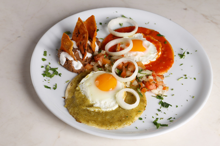 Huevos divorciados, fried eggs on corn tortillas with salsa verde and roja, mexican breakfast 스톡 콘텐츠