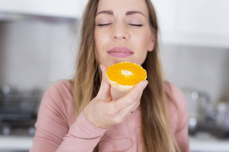 Beautiful young woman with fresh healthy oranges at kitchen 스톡 콘텐츠