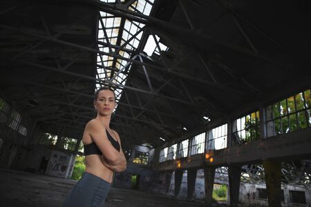 Attractive fitness girl posing in abandoned ruined factory 스톡 콘텐츠