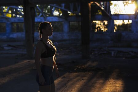 Fitness girl outdoors with low sunlight and shadows