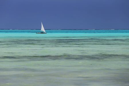 Wooden Fishing Boat with sail in turquoise waters of Indian ocean,Zanzibar,Tanzania 스톡 콘텐츠