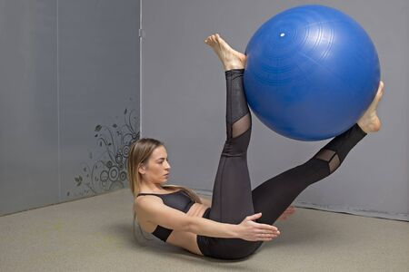 Fitness instructor demonstrates how to do the exercises in a gym with fitness ball