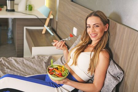 Healthy lifestyle woman eating fresh salad,stay at home