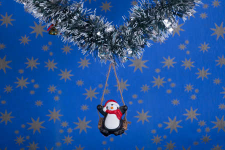 Creative layout,Christmas decorations,a penguin on a swing with starry sky background Stock Photo