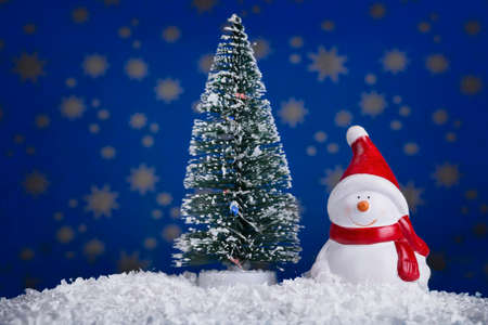 Snowman doll with Christmas tree on starry blue background Stock fotó