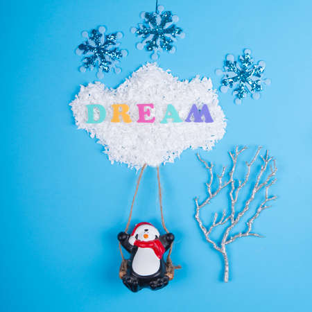 Creative layout with Christmas decorations,penguin swinging on a cloud