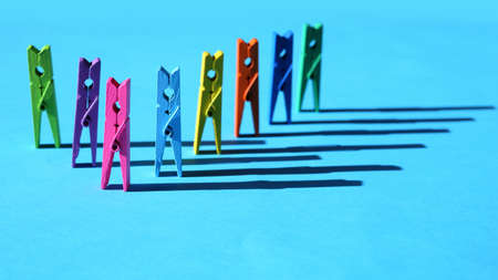 Colorful laundry clips arranged on blue background Standard-Bild