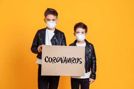 Covid-19 Coronavirus. Two boys wearing protective face masks and holding the sign