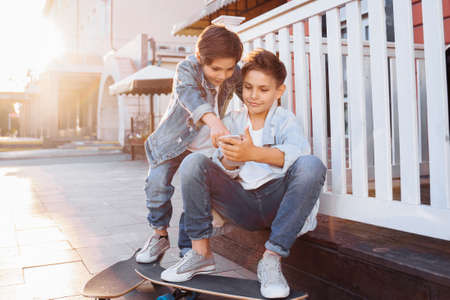 Two attractive caucasian teenagers, wearing denim jackets, pants and white T-shirts sitting near fence, looking to phone. Smiling, laughing, surprising, poking to gadget on evening summer sunset.