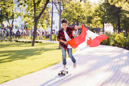 A young guy of 9 years old riding on a sunny road in the evening in the city park, dressed in a flannel plaid shirt. Holding fluttering flag of Canada. Happy Day Independence day to Canada.