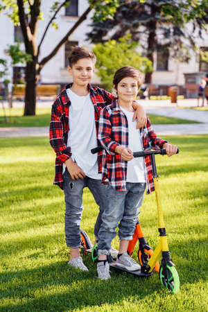 Two attractive european boys brothers, wearing red and white checkered flannel shirts, standing on scooters in the park. They laughing, smiling, hugging and having fun. Showing big fingers up sign.