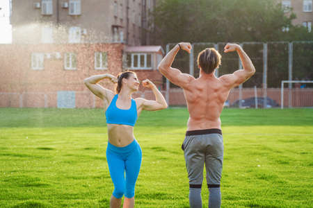 Exercises in pairs. Attractive athletes girl and guy demonstrating pumped up body. Guy is standing with a naked torso, girl is wearing a blue top and leggings. Showing muscles on the arms. 写真素材