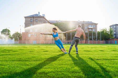 Fit young couple doing acro yoga in the park or on the field stadium. Man standing on the grass and balancing his woman on hands. Happy, sportive young athletes.