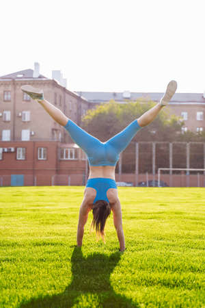 Incredibly beautiful, athletic girl does exercises at the sports city stadium on a warm summer evening. Making a stand upside down on hands.
