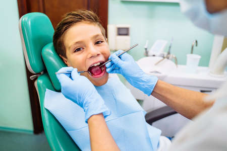 Effective solution to dental problems of teenager. Pediatric dentistry requires special attention and high competence. Tooth with caries. Bor machine effectively removes black spots on child's tooth.