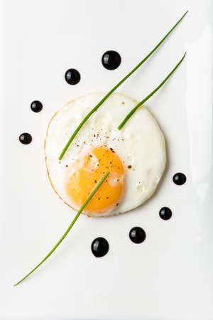 Egg omelette with balsamic vinegar chives and dots of balsamic vinegar on a white porcelain plate Stock Photo