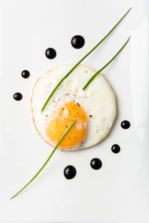 Egg omelette with balsamic vinegar chives and dots of balsamic vinegar on a white porcelain plate Stock fotó