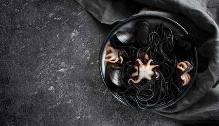 Concept Mediterranean delicacy food. Black seafood spaghetti pasta with octopus and mussels with gray napkin in a black plate on a dark background. Copy Space