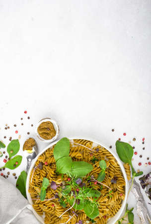 Green spinach pasta with microgreen and pesto and pepper in a white bowl with silver cutlery. Gourmet italian meal. Top view. Flatlay. Concept health eating