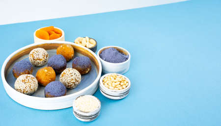 Homemade blue matcha energy balls in a ceramic bowl plate on a bright blue background top view, healthy sweets made of nuts and date, dried apricots, sesame, cashew nuts. Concept vegeterian diet sweet brain food. Copy space
