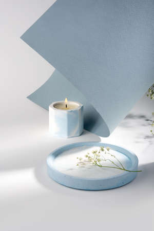 Creative composition with scented candles of soy wax in a concrete candlestick on a blue and white paper background. Eco-friendly. Minimalism. Natural. Dried flowers. Cozy atmosphere and shadow.
