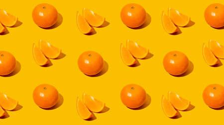 Fresh citrus Seamles fine pattern. Ripe fruit tangerines. Trendy sunlight Summer pattern made with mandarine slice on bright light orange background. Minimal summer concept. Monochromatic Banner.