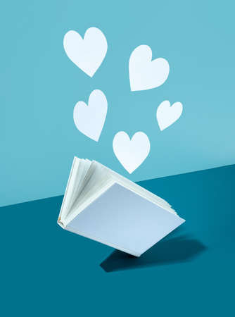 Floating Cute paper heart and white cover book on bold color blue-aquamarine-turquoise background. Modern photo. Concept National Book Lovers Day. happy holydays.Romantic, love storytelling.copy space