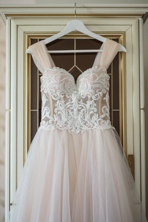 fine art beautiful wedding dress on hanger on a wall. Beautiful gown Stock fotó