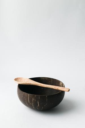 Handmade coconut shell bowl and wood spoon on white background, stylish minimalism