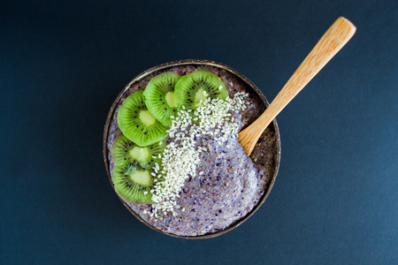 Healthy smoothie with fruits, plate made from coconut shell and wood spoon. Kiwi, banana, black currant