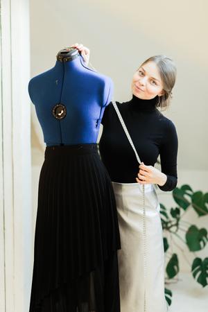 Eine junge Näherin legt Kleidung auf die Schaufensterpuppe. Porträt der Näherin und ihrer Handnahaufnahme im Studio. Konzentrieren Sie sich auf die Schaufensterpuppe mit Kleidung Standard-Bild