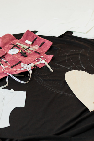 sewing kit accessories in pink cover and black fabric on the floor Banque d'images
