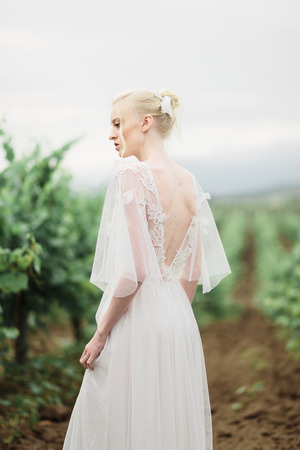 Portrait of a gorgeous women in the vineyards. Happy bride and groom